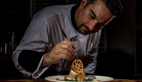Chef at beachfront luxury Mykonos Blanc hotel preparing a delicious meal.