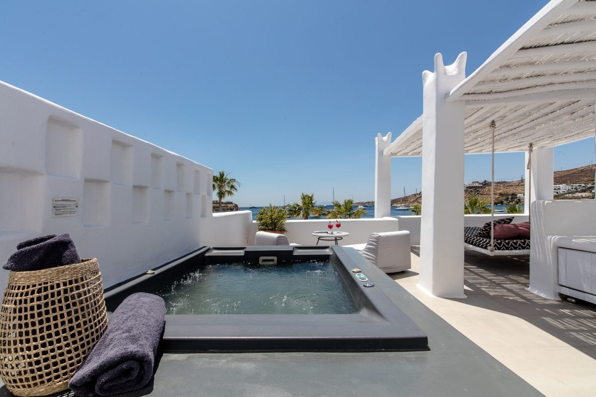 Outdoor jacuzzi and pergola shaded area overlooking the sea at Mykonos Blanc Hotel.