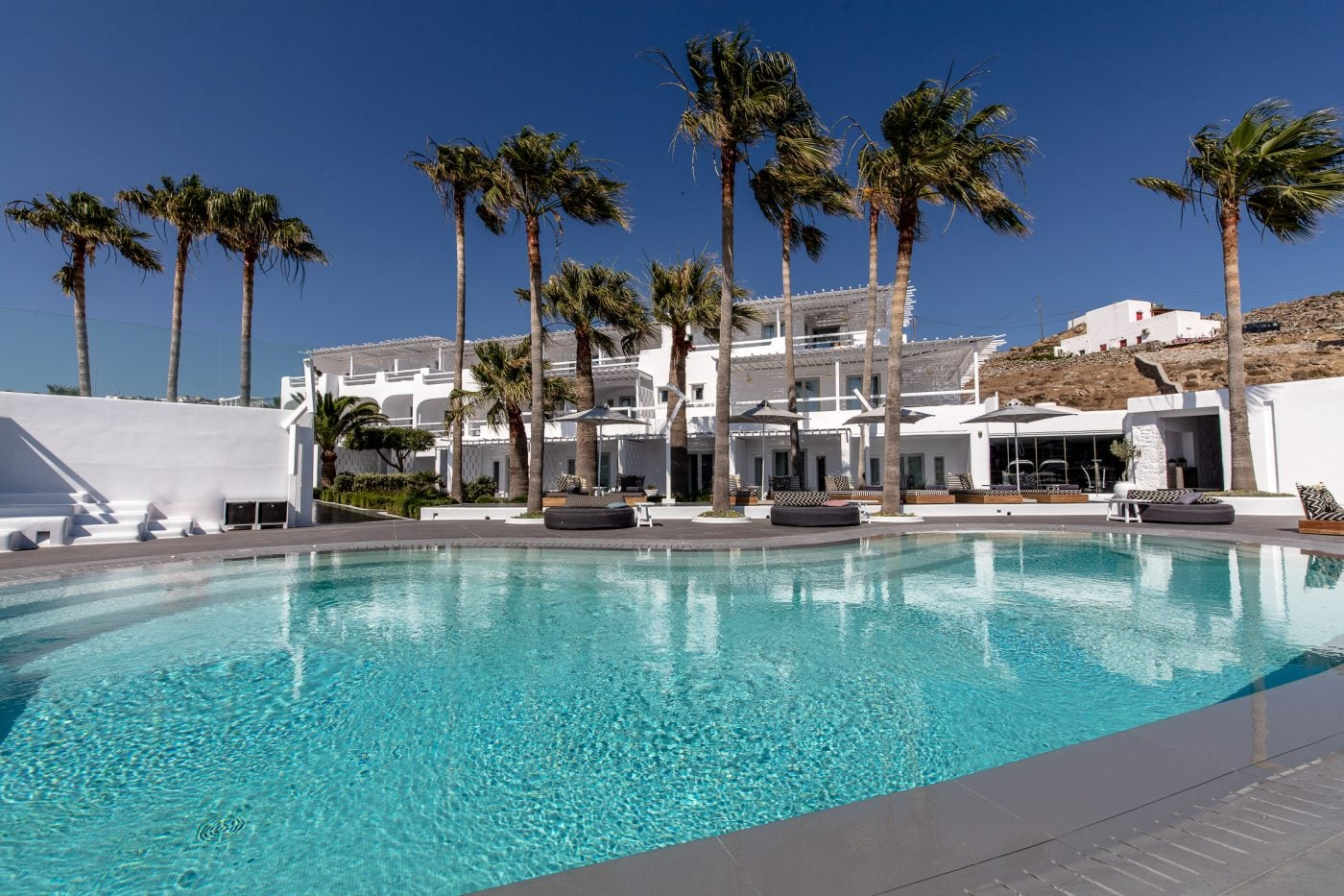 Palm trees and sunbeds by the pool at the 5- sta beachfront luxury Mykonos Blanc Hotel.
