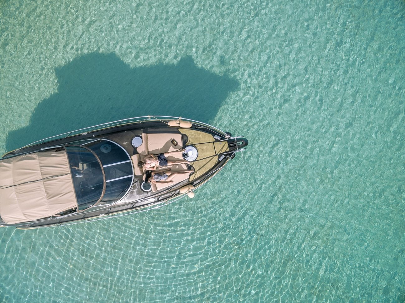 Overhead view of a boat sailing on the Aegean sea in Ornos, Mykonos.