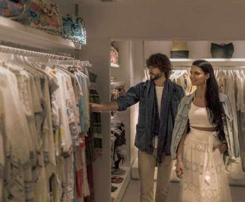 A young couple is buying clothes at the unique Go Blanc Boutique.