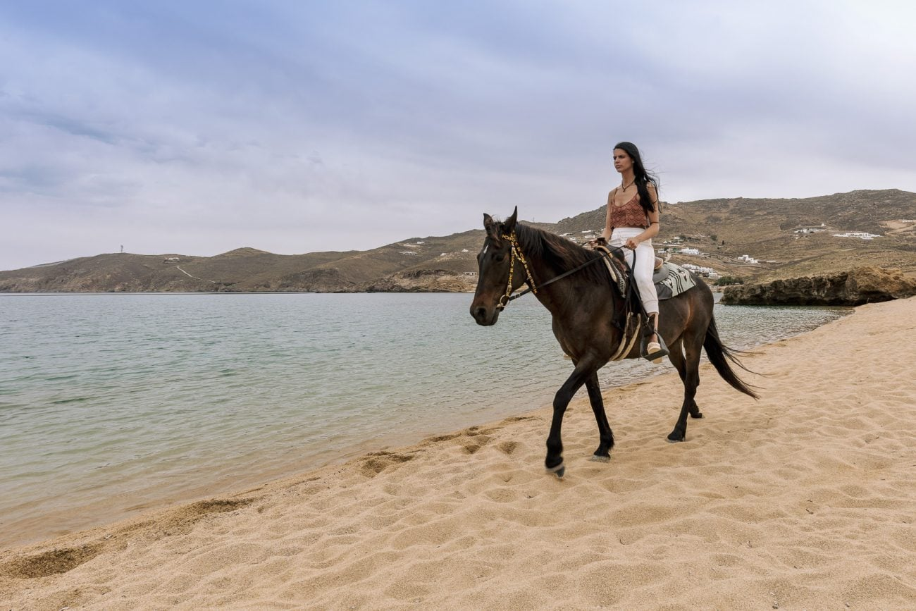 Lady riding a horse riding on the sea in Mykonos. Golden sand and amazing sea view.