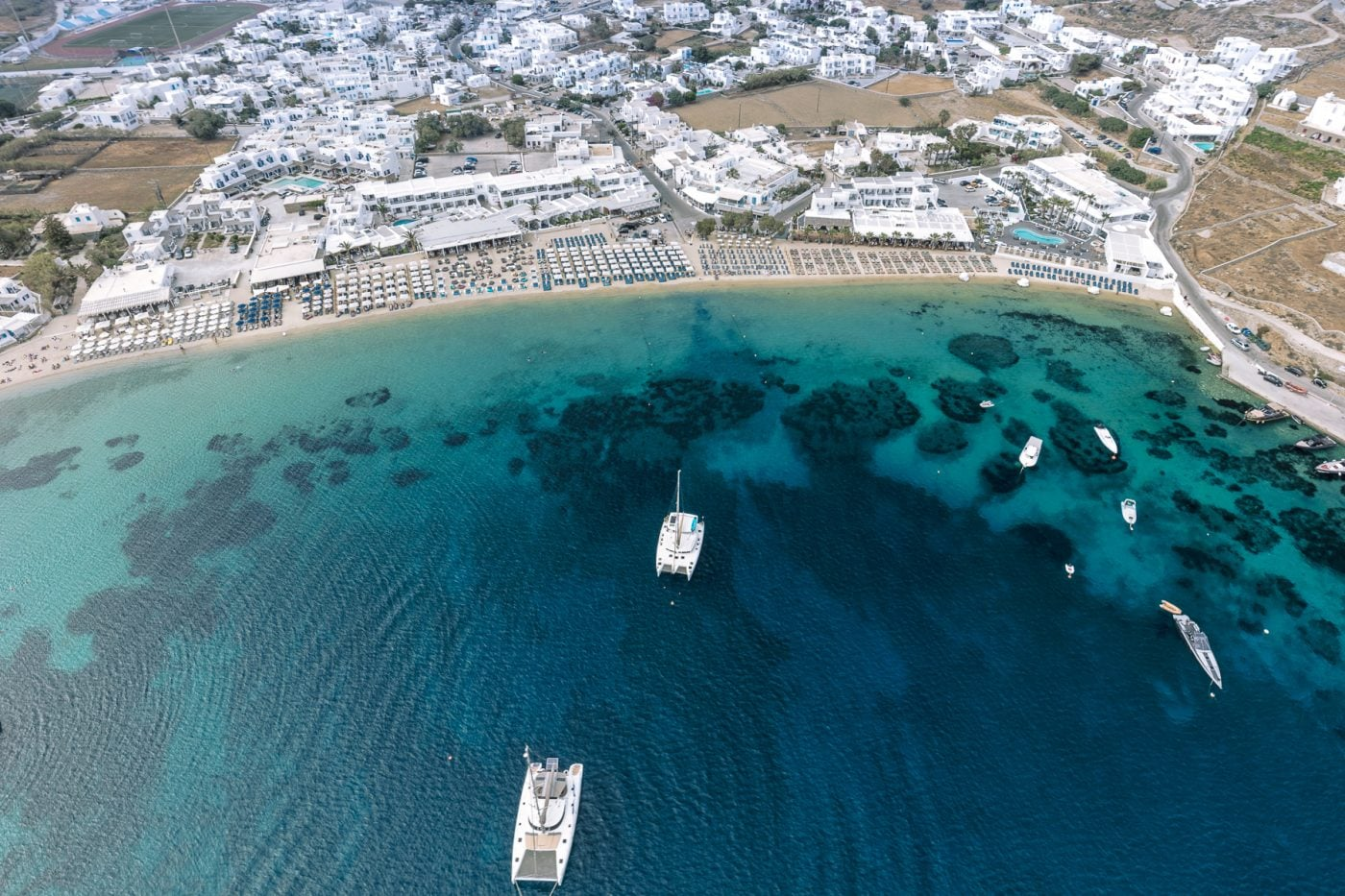 View of the Ornos bay in Mykonos as seen by a drone. Crystal clear sea and white coloured houses.
